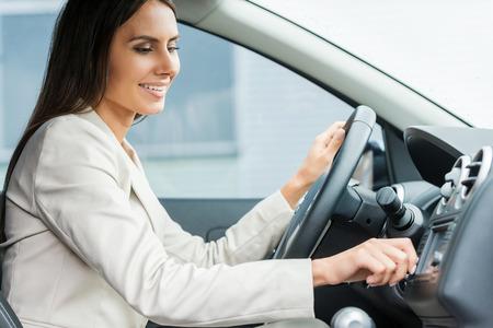 Rijden met comfort. Zijaanzicht van mooie jonge man in formalwear rijdende auto en ontroerende dashboard met de vinger Stockfoto