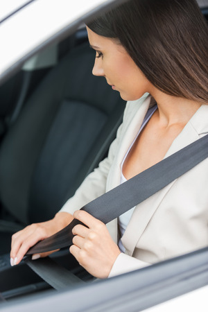 car safety: Fastening her seat belt. Confident young businesswoman fastening seat belt while sitting in his car