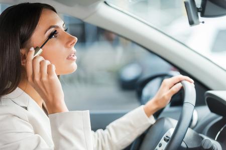 부주의 한 운전사. 자동차 운전하는 동안 formalwear에서 젊은 여자의 측면보기 메이크업 하 고