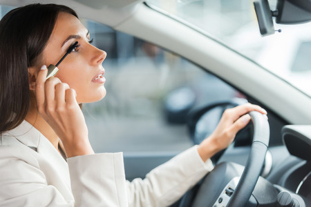 careless: Careless driver. Side view of young woman in formalwear doing make-up while driving a car