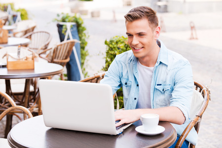 attractive man: Using advantages of free Wi-Fi. Handsome young man working on laptop and smiling while sitting in sidewalk cafe