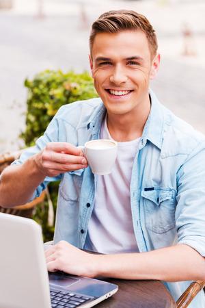 hombre tomando cafe: Pasar tiempo en la cafeter�a. Joven alegre que trabaja en la computadora port�til y el consumo de caf� mientras estaba sentado en la acera caf�