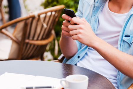 mobile shop: Chatting with friends. Close-up of young man holding mobile phone while sitting in sidewalk cafe Stock Photo