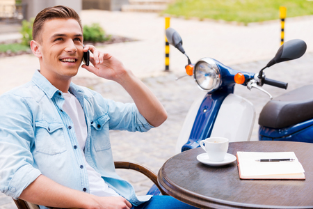 sidewalk talk: Good talk with friend. Relaxed young man talking on the mobile phone and smiling while sitting in sidewalk caf� with scooter in the background Stock Photo