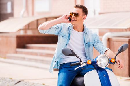 vespa piaggio: Bella chiacchierata con l'amico. Allegro giovane uomo seduto su scooter e parlando al telefono cellulare Archivio Fotografico
