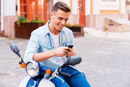 one young man: Typing a message to friend. Cheerful young man sitting on scooter and looking at his mobile  Stock Photo