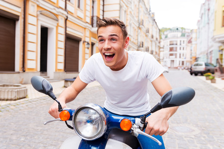 Testing his new scooter. Happy young man riding scooter along the street and keeping mouth open