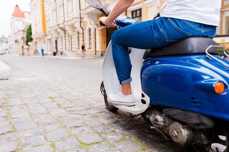 vespa piaggio: Cavalcando il suo nuovo scooter. Vista posteriore ritagliata immagine di giovane uomo equitazione scooter lungo la strada