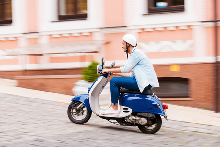 man side: Enjoying his scooter ride. Side view of young man in helmet riding scooter along the street  Stock Photo