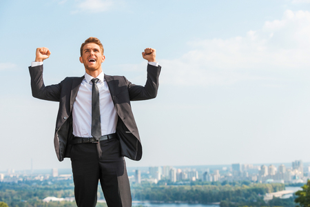 arms raised: Business winner. Happy young man in formalwear keeping arms raised and expressing positivity while standing outdoors with cityscape in the background Stock Photo