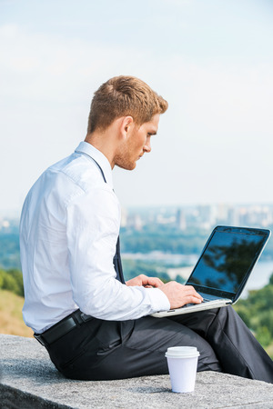 top of the world: Having freedom to work everywhere. Rear view of confident young man in shirt and tie working on laptop while sitting outdoors with cityscape in the background