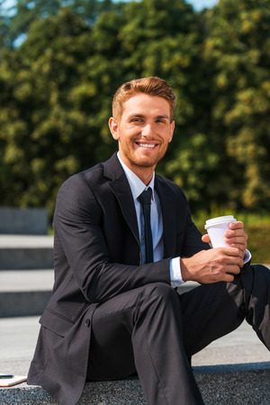 only man: Enjoying his coffee break. Handsome young man in formalwear drinking coffee and smiling while sitting outdoors