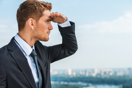 Looking for new business opportunities. Thoughtful young man in formalwear holding hand on forehead and looking away while standing outdoors with cityscape in the background Stock Photo