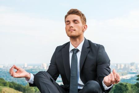Zakenman mediteren. Ontspannen jonge man in formalwear mediteren zittend in lotushouding met stadsgezicht in de achtergrond