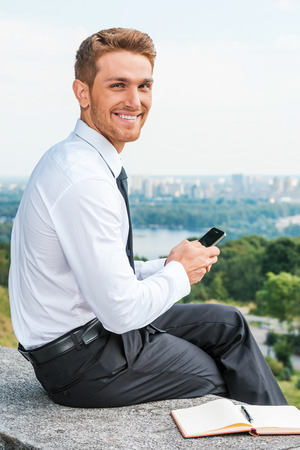 Staying connected anytime and anywhere. Confident young man in shirt and tie holding mobile phone and smiling while sitting outdoors with cityscape in the background Stock Photo