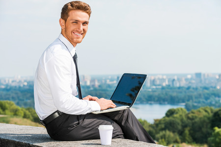 everywhere: Having freedom to work everywhere. Confident young man in shirt and tie working on laptop and smiling while sitting outdoors with cityscape in the background Stock Photo