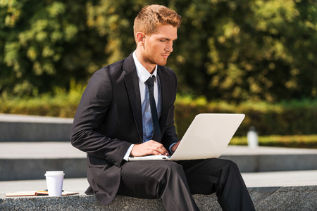 only adult: Working outdoors. Confident young man in shirt and tie working on laptop while sitting outdoors  Stock Photo