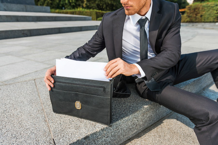 business briefcase: This is exactly what I need. Close-up of confident young man in formalwear taking the documents from briefcase while sitting outdoors Stock Photo