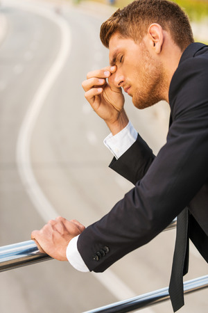 Depressed businessman. Depressed young man in formalwear touching his nose and keeping eyes closed while standing outdoors and leaning at the metal railing photo