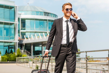 Executive on the Go. Handsome young businessman in full suit carrying suitcase and talking on the mobile phone while walking outdoors photo