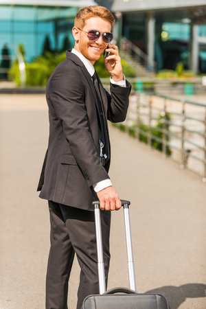 just arrived: Just arrived. Cheerful young businessman in full suit carrying suitcase and talking on the mobile phone while walking outdoors