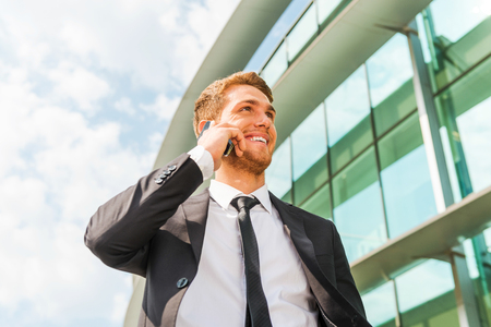 Confident business talk. Cheerful young man in formalwear talking on the mobile phone and looking away while standing outdoors and against building structure photo