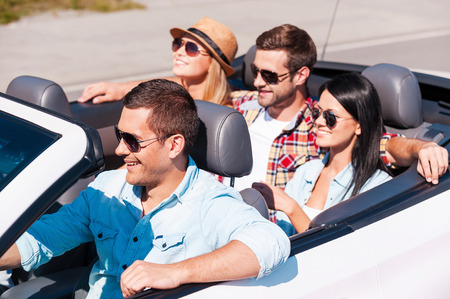 Fun travel. Top view of young happy people enjoying road trip in their white convertible photo