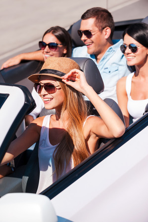 Nothing but friends and road trip. Top view of young happy people enjoying road trip in their white convertible photo