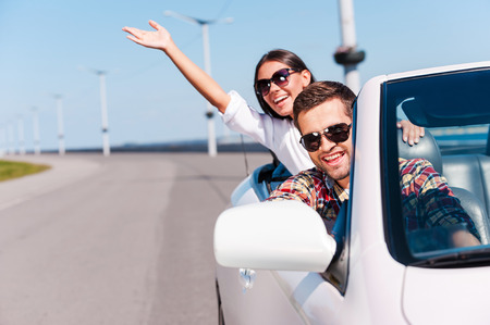road trip: Traveling with fun. Happy young couple enjoying road trip in their white convertible