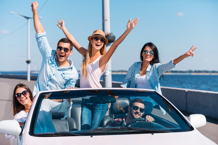 Spending great time in convertible. Group of young happy people enjoying road trip in their white convertible and raising their arms Stock Photo