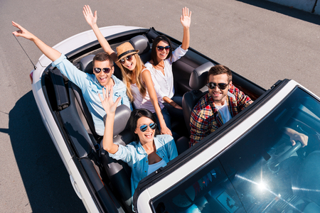 Traveling with fun. Top view of young happy people enjoying road trip in their white convertible and raising their arms photo