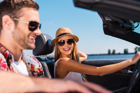 Having freedom to go anywhere. Beautiful young couple enjoying road trip in their convertible while beautiful woman looking at her boyfriend and smiling photo