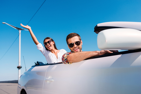 Traveling with fun. Happy young couple enjoying road trip in their convertible while woman raising arms and smiling  photo