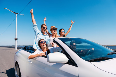 driving: Nothing but friends and road ahead. Group of young happy people enjoying road trip in their white convertible and raising their arms up Stock Photo