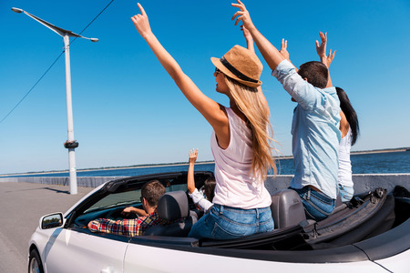 Traveling together is great fun. Rear view of young happy people enjoying road trip in their convertible and raising their arms up photo