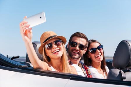 people  camera: La captura de un momento feliz. Tres j�venes felices disfrutando de viaje por carretera en su convertible blanco y haciendo Autofoto