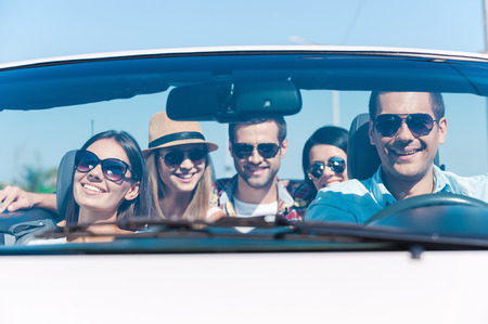 We always travel together! Group of young happy people enjoying road trip in their white convertible photo