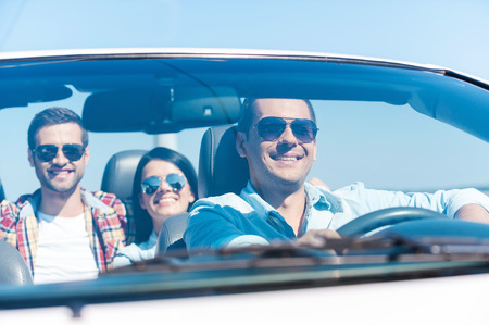man front view: We love traveling together! Group of young happy people enjoying road trip in their white convertible