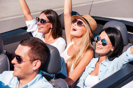 Enjoying their road trip. Top view of young happy people enjoying road trip in their white convertible photo