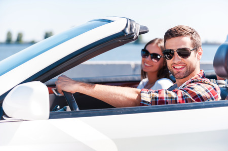 Traveling with comfort. Happy young couple enjoying road trip in their white convertible while both looking at camera and smiling photo