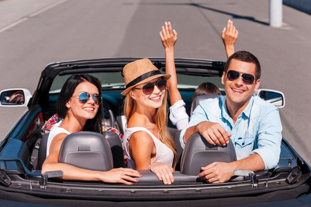 Nothing but friends and road trip. Top view of young happy people enjoying road trip in their white convertible and smiling photo