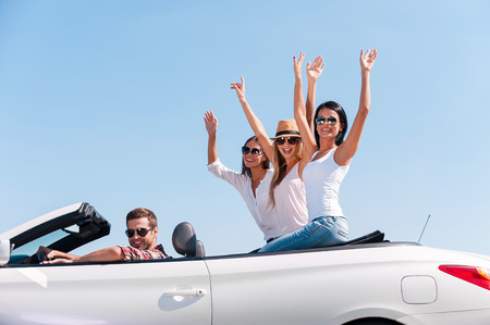Spending great time together. Group of young happy people\ enjoying road trip in their white convertible while girls raising\ arms and smiling