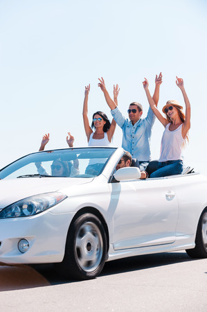 Friends and road trip. Group of young happy people enjoying road trip in their white convertible while raising arms and smiling photo