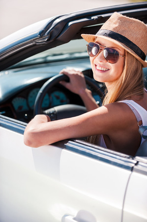 Beauty in convertible. Beautiful young funky woman in sunglasses sitting on front seat of her convertible and smiling  photo