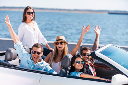 Great day for a ride. Group of young happy people enjoying road trip in their white convertible and raising their arms photo