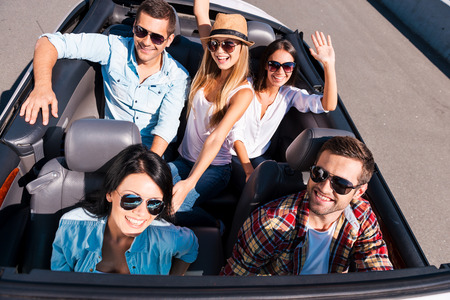 We always travel together. Top view of young happy people enjoying road trip in their white convertible and raising their arms photo