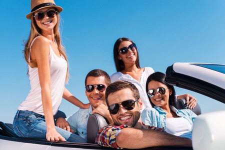 The best friends ever. Group of young happy people enjoying road trip in their white convertible  photo