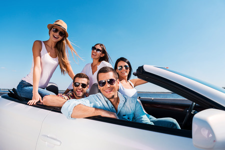 We love spending time together! Group of young happy people enjoying road trip in their white convertible and smiling at camera photo