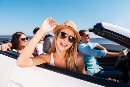 도로 여행을 즐기고있다. 자신의 흰색 컨버터블 도로 여행을 즐기는 젊은 행복한 사람들의 그룹