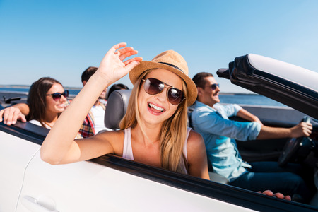 Enjoying road trip. Group of young happy people enjoying road trip in their white convertible Standard-Bild